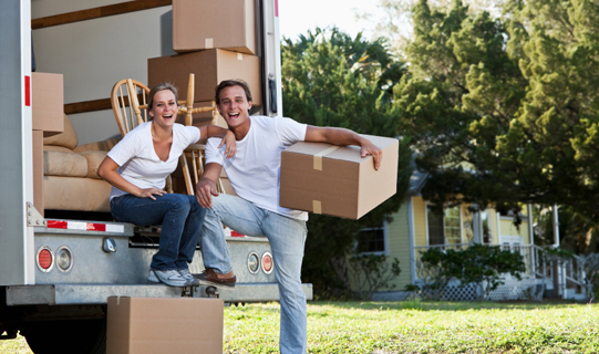 Couple taking a break loading or unloading moving van with boxes and furniture